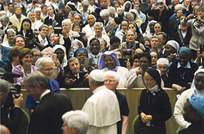 Sr Margaret Anne Mills (standing left) talking with Pope Francis.