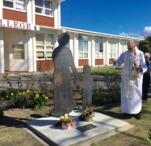 Monsignor John Carde blesses the iron silhouette standing at Chanel College in honour of Masterton's CWL pioneers
