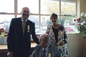 Gordon and Linda Holmes and Pat Hewson (seated) receive papal award for Church dedication.