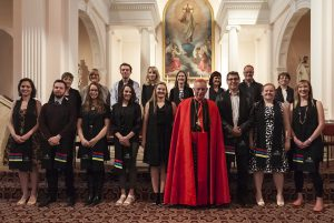 Group of TCI 2016 graduating students with Cardinal John. From left, back: Fiona Rammell, Deborah Matheson, Maurice Atkinson, Emma Dodsworth, Michelle Teahan, Raewyn Sullivan-Brown, Sean Ryan, Christine McDonald. From left, front: Hannah Gilmour, Reuben Fletcher, Roseanne Fletcher, Kathleen Scott-Mead, Eliana King, (Cardinal John Dew), Michael Draper, Katherine Sprowson, Ariana Kooge.